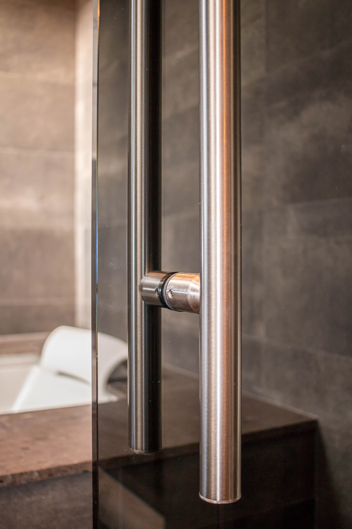 Close-Up of Polished Stainless Steel Handle on Grey Glass Bathroom Door